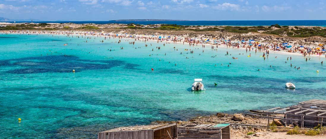 Aguas cristalinas y bañistas en la playa ses illetes en Formentera en las Islas Baleares