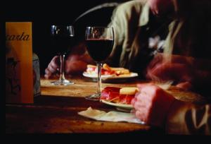 copas de vino y jamon en una mesa de las bodegas pipi de Málaga