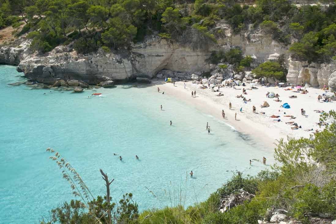 bañistas y aguas cristalinas en Cala Mitjana en Menorca