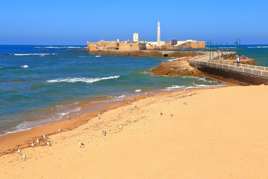 paseo hacia el castillo de san sebastian en la Playa de la Caleta de Cadiz