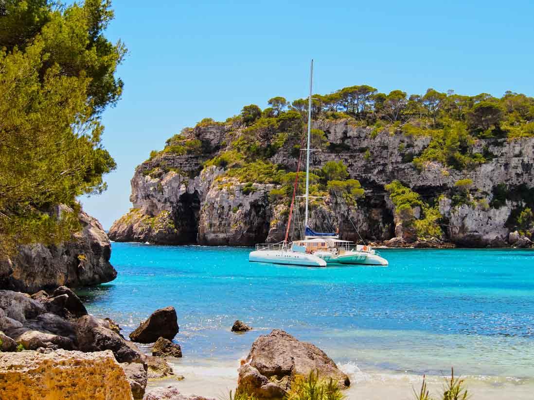 barco navegando en la cala macarella de Menorca