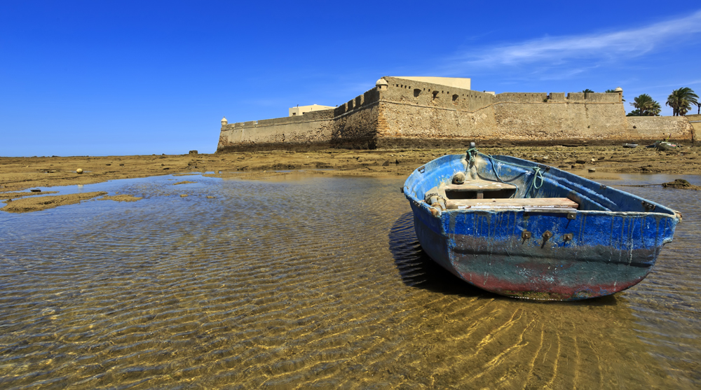 View of the castle of Santa Catalina with aged ship on forefront, Cadiz, Andalusia, Spain