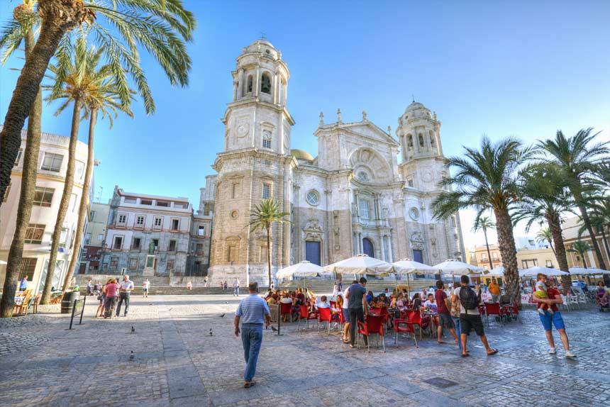 Bonita plaza con terrazas, palmeras y la Catedral de Cadiz