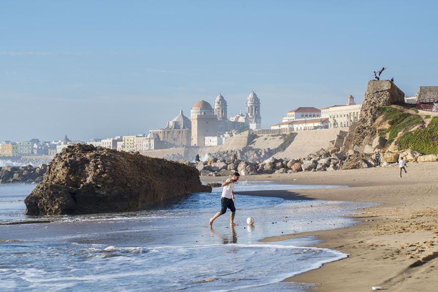 niño jugando en la playa de Santa Maria del Mar con la catedral de Cadiz como telon de fondo