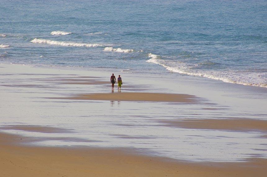 Pareja paseando por la playa de los Bateles en Conil de la Frontera