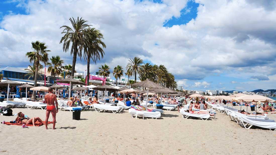Tumbonas y gente tomando el sol en Playa den Bossa, Ibiza