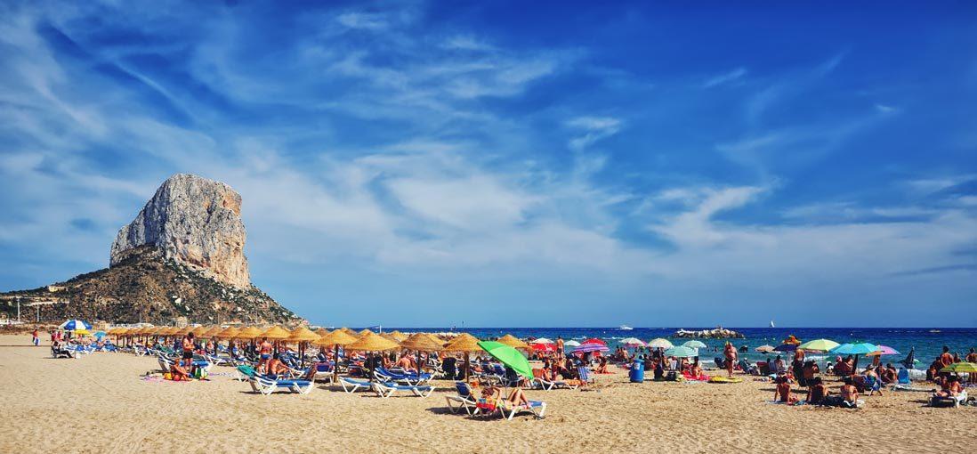 Playa llena de bañistas en Calpe junto al Peñon de Ifach