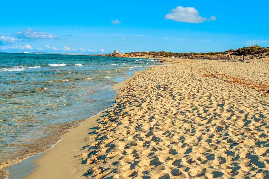Playa Es Cavallets y la torre de ses portes al fondo