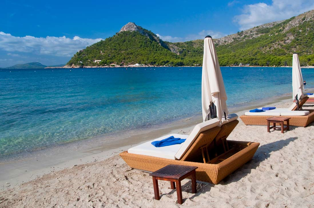 tumbonas de lujo frente a las aguas cristalinas de la playa de Formentor en Alcudia al norte de Mallorca