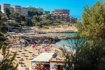 playa llena de bañistas en la playa Cala Font en Salou durante el verano