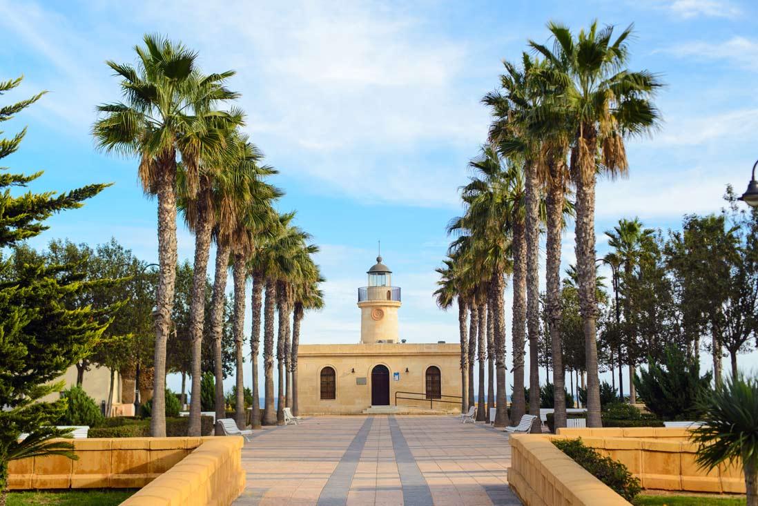 Vista frontal del faro de Roquetas de Mar rodeado de palmeras en ALmeria
