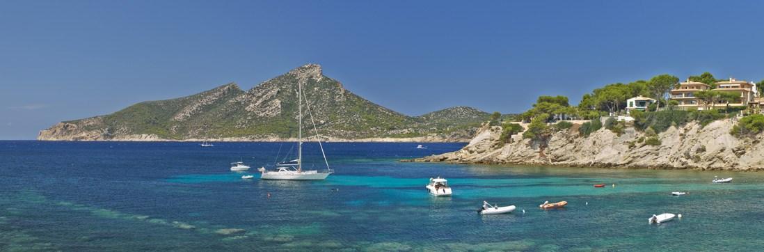 barcos navegando en las aguas cristalinas del parque natural Sa Dragonera en Mallorca