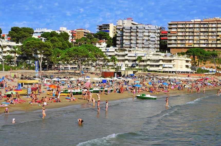 Playa dels Capellans en el centro de Salou abarrotada de gente durante un caluroso dia de verano