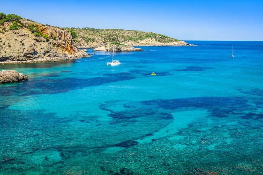 Boats and turqois waters in Cala Benirras beach