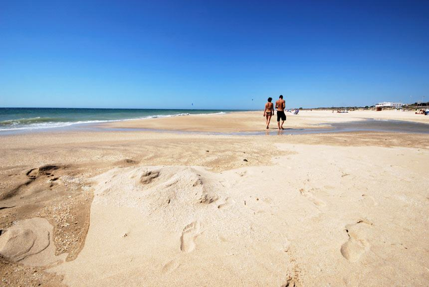 People walking on the sand in El Palmar beach