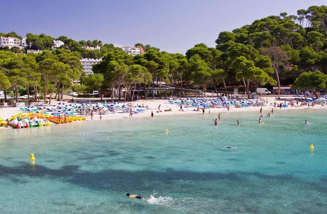 Beach cala Galdana full of people on Summer in Menorca