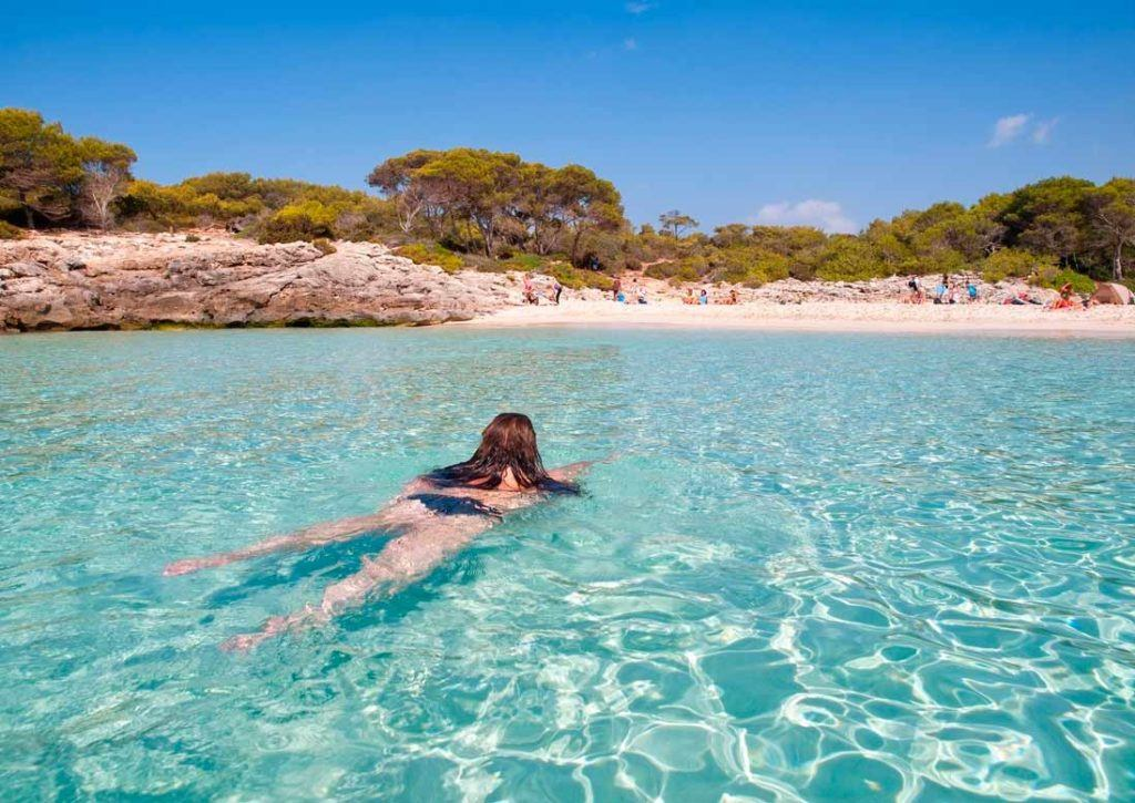 Woman swiming in turquois and cristaline waters of Cala Talaier