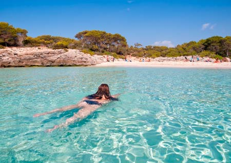 woman swiming in turquois waters in Cala Talaier