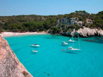 Panoramic view Cala Macarella , boats and green forest with turquois waters